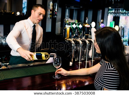 Barman serving a glass of wine in a bar - stock photo