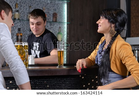 Barman socialising with customers at the bar laughing and smiling as he chats to a young man and woman