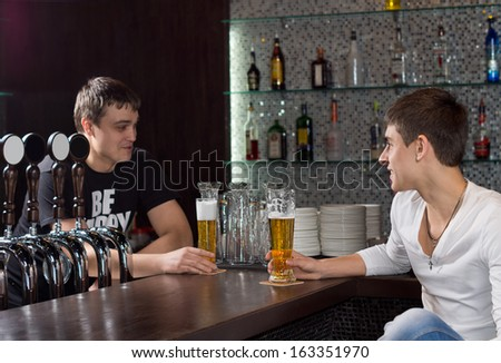 Barman standing behind the counter in a pub chatting to a customer as they enjoy a pint of beer together - stock photo