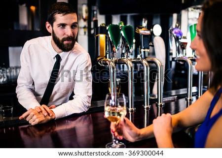 Barman talking with pretty customer in a bar - stock photo