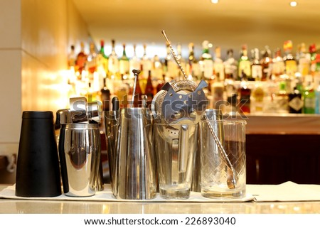 barman tools against alcoholic bottles in the background - stock photo