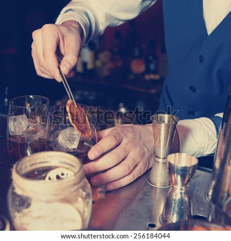 Barman works at bar counter, blue toned image - stock photo