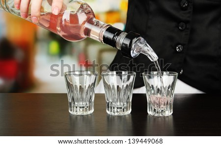 Barmen hand with bottle  pouring beverage into glasses, on bright background - stock photo