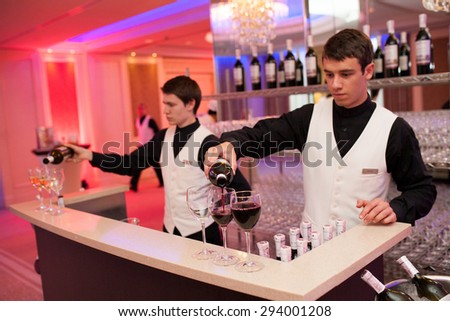 Barmens spill wine at the bar - stock photo