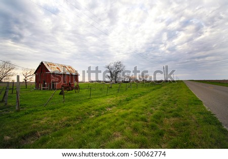 barn and old tractor and a country road. - stock photo