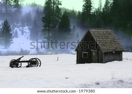 Barn and old wooden wagon in the snow - stock photo