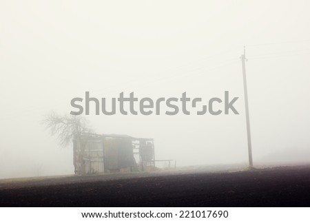 Barn and pillar in fog. Rural landscape. Loneliness. Sad mood - stock photo