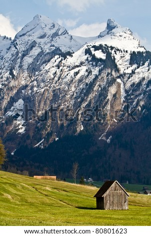 Barn and snowy peaks in the background - stock photo