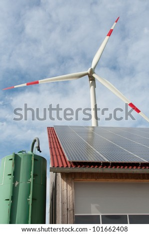 barn covered with solar panels and wind turbine in the background - stock photo