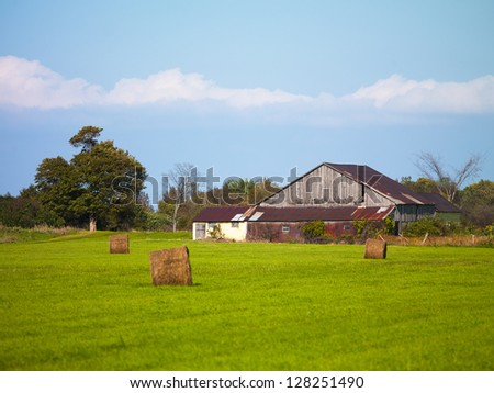 Barn in hay field with blue sky in the background. - stock photo