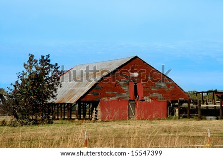 Barn is surrounded by golden field.  Antlers are mounted under the eaves.
