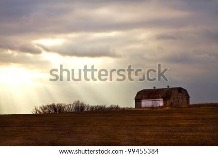 Barn on Farm Land Basking in Rays of Sunlight - stock photo