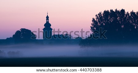 Baroque church in the foggy morning, colorful sky. Tursko, Bohemia, Czech Republic. - stock photo