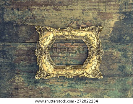 Baroque golden frame over rustic wooden background. Grunge wood texture. Vintage style toned picture - stock photo