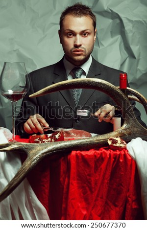 Baroque supper of blue blood aristocrat. Portrait of handsome man eating fresh meat at vintage restaurant. Retro accessories: deer horn, red & white table sheet. Luxury style. Indoor shot - stock photo