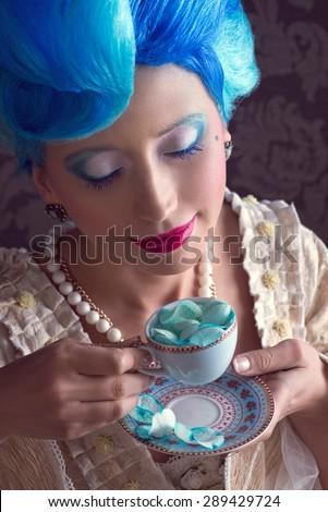 Baroque woman  with blue hair enjoying her tea - stock photo