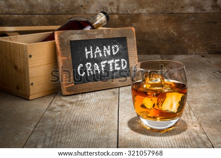Barrel aged craft liquor spirits glass ice bourbon whisky scotch brandy rum on wood bar table whiskey - stock photo