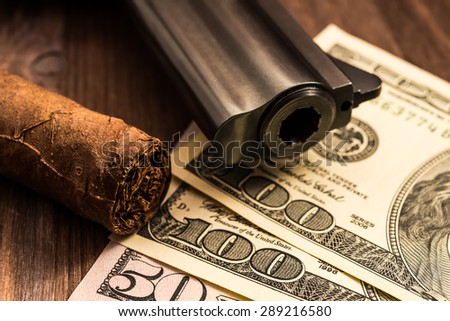 Barrel of a revolver with cuban cigar and money on the wooden table. Close up view, focus on the cuban cigar - stock photo