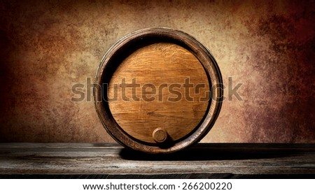 Barrel on a wooden table and brown background - stock photo