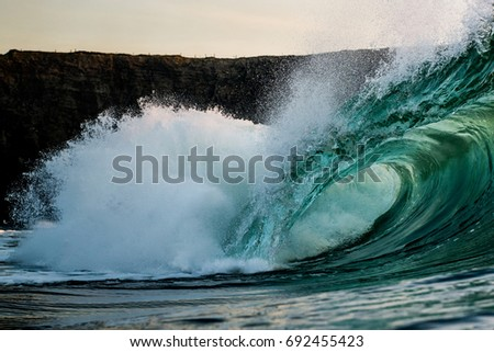Barreling surf wave breaks in the ocean in front of cliff