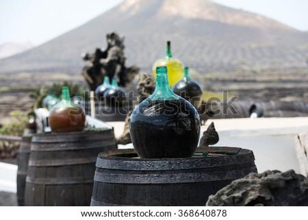 Barrels and  big bottles with grape wine - malvasia.  Lanzarote, Spain - stock photo