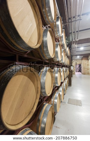 barrels in rows at contemporary wine factory  - stock photo