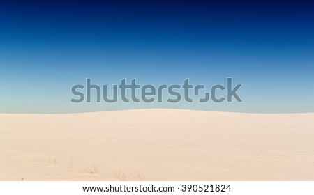 Barren and empty winter landscape scene with minimal elements in the frame. Nobody in the scene. Snow covered fields with a clear blue wintry sky with no clouds. Copy space area for travel or seasonal - stock photo
