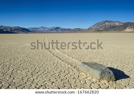barren vista of The Racetrack at Death Valley National park showing one of the mysterious wandering rocks