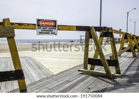 Barricades and a danger sign warn people to keep away on the Asbury Park boardwalk.  Photo taken on April 9, 2013 - just over six months after Hurricane Sandy hit New Jersey. - stock photo