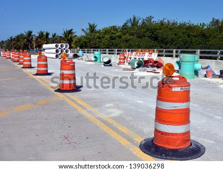 Barricades And Large Sewer Pipes On A Road Construction Site - stock photo