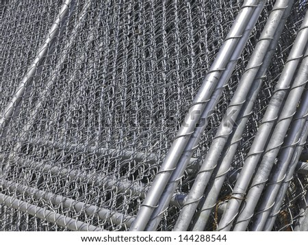 Barriers in abundance: Stack of chain-link fencing on construction site - stock photo