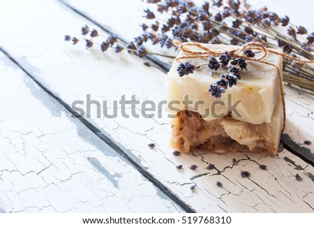 Bars of handmade soap with lavender flowers over white wood grunge background.