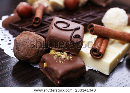 Bars of white and bitter chocolates with candies, hazelnut and cinnamon stick on the dark wooden smooth background with doily - stock photo
