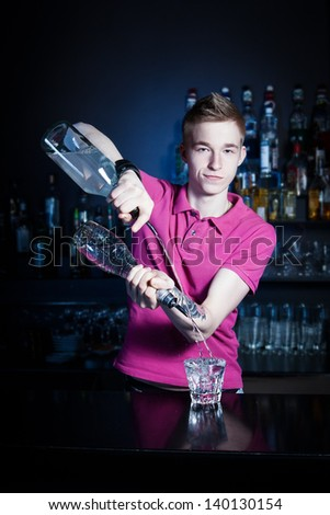 Bartender bartender is pouring a drink and looking at the camera - stock photo