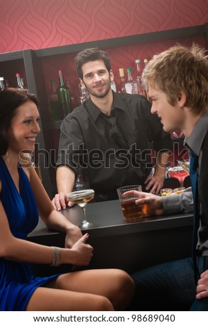 Bartender behind the bar couple chatting and have drink - stock photo