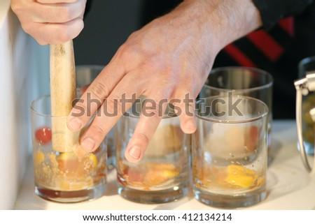 Bartender crushing fruit for cocktails. - stock photo