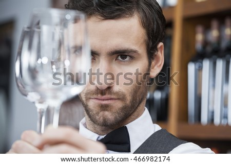Bartender Examining Wineglass At Winery