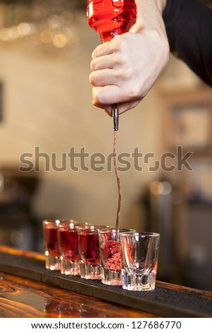 bartender fills a few glasses in a row at the same time - stock photo