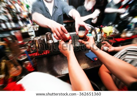 Bartender gives ready cocktails. alcoholic beverage in his hand - stock photo