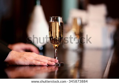 Bartender holding glass with champagne, close-up - stock photo