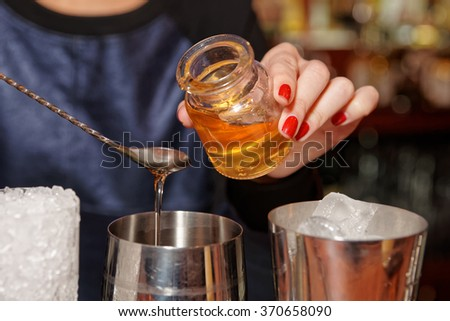 Bartender is adding honey to the mixing glass - stock photo