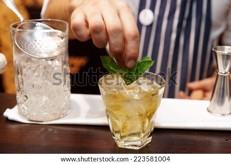 Bartender is adding mint to the cocktail - stock photo