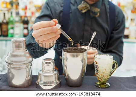Bartender is making cocktail at bar counter, adding some bitter in the shaker - stock photo