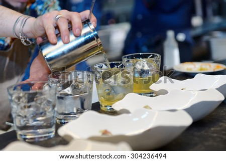 Bartender is making cocktail at bar counter, blue toned image - stock photo