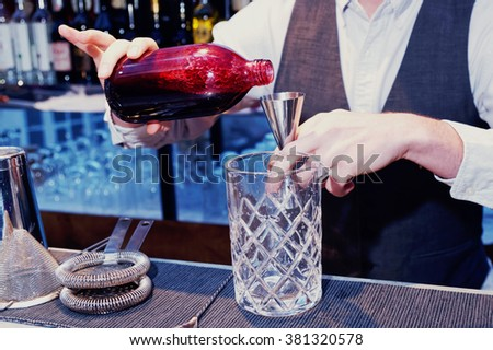 Bartender is pouring black currant shrub in mixing glass, toned image - stock photo