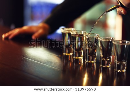 Bartender is pouring tequila into glass - stock photo