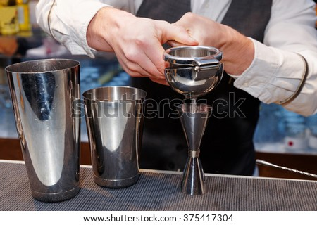 Bartender is squeezing citrus juice in jigger - stock photo