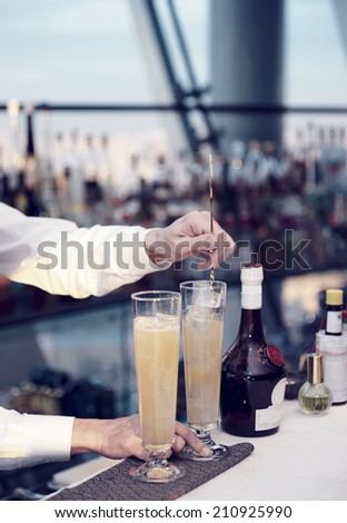 Bartender is stirring a cocktail, sunset light, toned image - stock photo