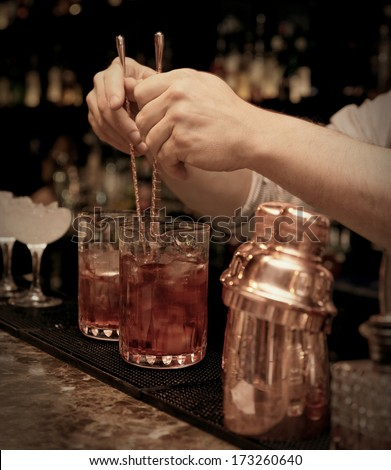 Bartender is stirring cocktails in mixing glasses - stock photo