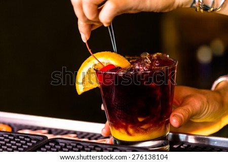 Bartender making Red Sangria in Italian restaurant. - stock photo